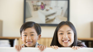 Two young children in dental waiting room with flat screen TV